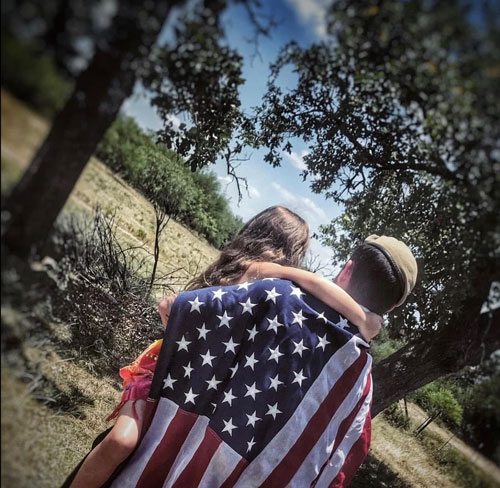 Ryan-Normandin-wearing-flag-with-daughter